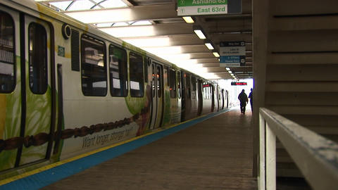 Passengers exit a colorful commuter train before it departs as another train arrives at the station Footage