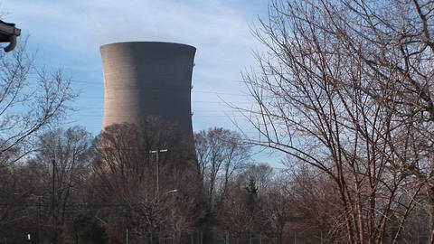 The camera pans from the front porch of a residential home to a nuclear power plant located nearby Footage