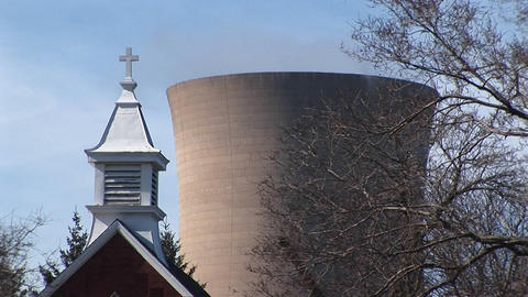 Camera focuses on a church steeple and a nuclear power plant in close proximity Footage