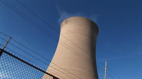 Steam drifts slowly from the top of a nuclear power plant Stock Video Footage
