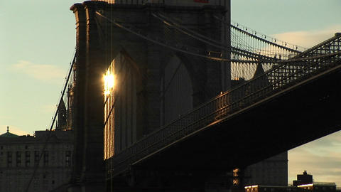 The sunlight from a building behind the Brooklyn Bridge shines through the infrastructure to create Footage