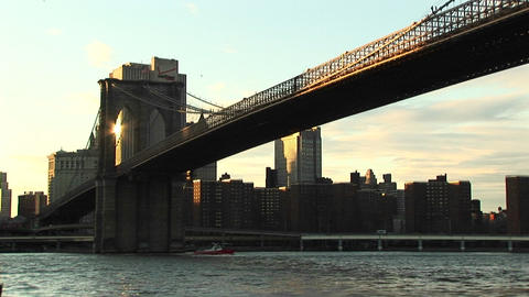The camera shoots from water-level to the Brooklyn Bridge above and buildings beyond Footage