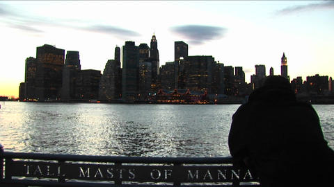 A tourist leans over boat railing and looks across the river toward the South Street Seaport shore o Footage
