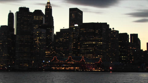 The camera pans from the south tip of Manhattan to the lights on the Brooklyn Bridge at the golden-h Footage