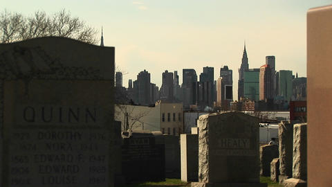 A pan of tombstones from a cemetery in Brooklyn stops with the Manhattan skyline perfectly framed Footage