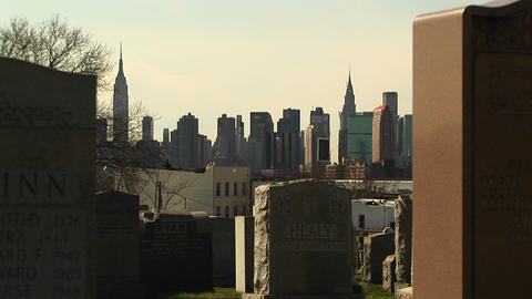 The New York City skyline is framed between two headstones in a Brooklyn cemetery Footage