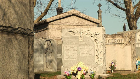 The camera pans through an old cemetery's tombstones and mausoleums Footage
