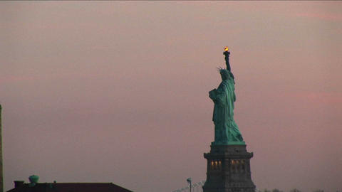 A striking view of the Statue of Liberty against a pale pink sky Footage