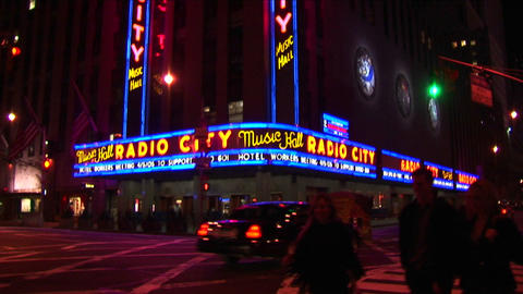 Radio City Music Hall at night with lights, traffic and pedestrians Footage
