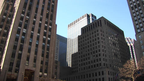 Camera pans up from the ice-skating rink for a worms-eye view of surrounding skyscrapers Footage