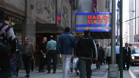 Medium-shot Of People Walking Under The Radio City Music Hall Marquee In New York City, New York stock footage