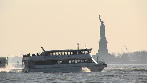 Passenger ferries pass each other in New York Harbor with the Statue of Liberty in the background Footage