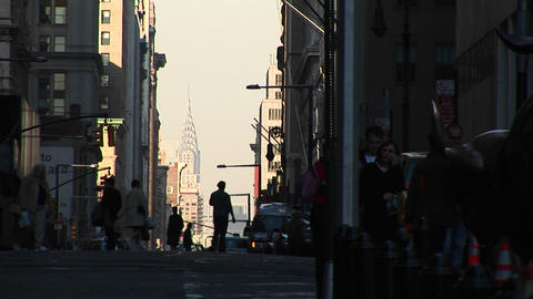 A busy street scene with pedestrians silhouetted in the foreground and skyscrapers rising above all Footage