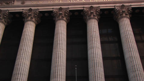 The camera pans up the columns of the New York Stock Exchange building to the inscription and frieze Footage