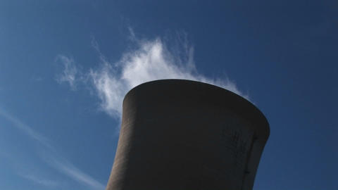 Steam slowly dissipates from the top of a nuclear power... Stock Video Footage