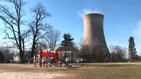 A children's colorful playground is seen in the foreground with a nuclear-power plant in the backgro Footage