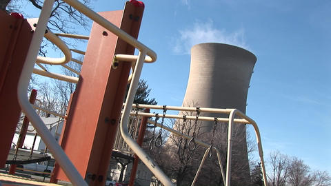 Children's playground equipment is being used while a nuclear-power plant is shown in the background Footage