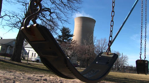 A child's swing, residential homes, and a nuclear power... Stock Video Footage