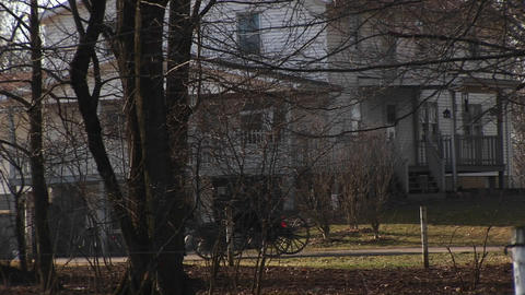 An Amish buggy travels by a large rural home Footage