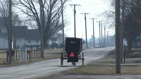 An Amish horse and carriage travel along a quiet country... Stock Video Footage