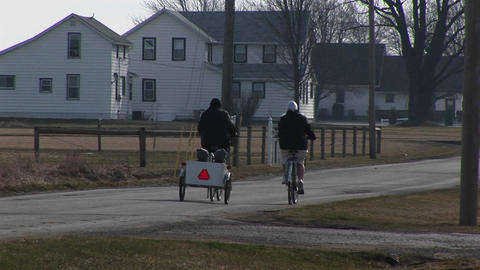 young people on bikes pull two very young kids in a child carrier Footage