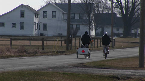 young people on bikes pull two very young kids in a child... Stock Video Footage