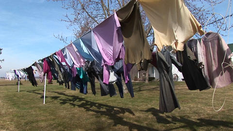 Colorful clothes hang on an outdoor clothesline to dry Stock Video Footage