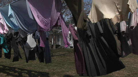 Colorful shirts and dark dresses hang on a clothesline to... Stock Video Footage