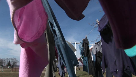 The camera pans through clothes hanging outdoors to dry in a rural community Footage