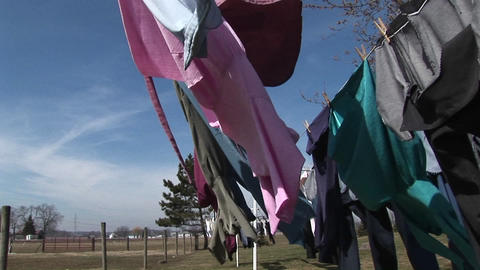 The camera pans through clothes hanging outdoors to dry... Stock Video Footage
