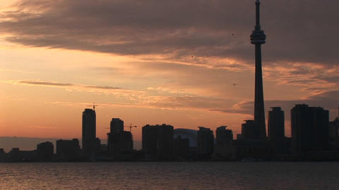 A spectacular sunset with the CN-Tower and other buildings nearby silhouetted against the colorful s Footage
