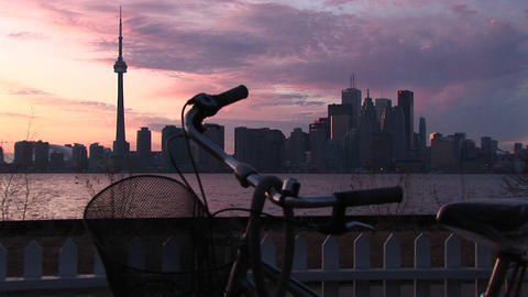 A bicycle is parked near the coastline of Lake Ontario with the skyline of Toronto in the background Footage