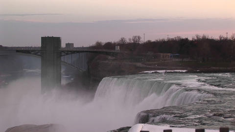 A moody view of Niagara Falls and bridge during golden-hour Stock Video Footage