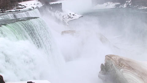 The camera looks down on Niagara Falls with a large ice chunk in the foreground Footage