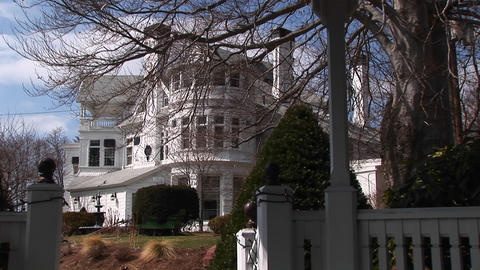 A picturesque mansion sits behind a white fence and gate Stock Video Footage