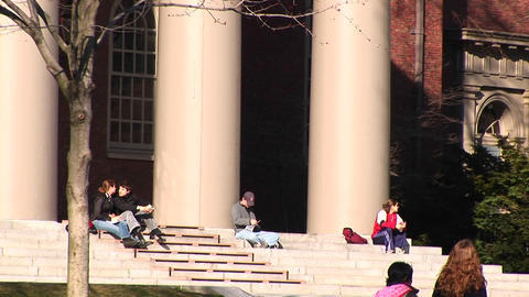 Students sit on the steps of the church at Harvard University Footage