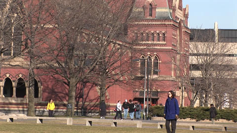 Students walk across campus as the camera pans up one of... Stock Video Footage