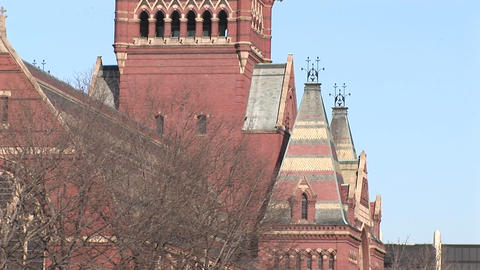 Students walk across campus as the camera pans up one of Harvard's churches Footage