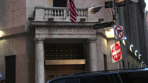 The camera pans up from the bronze door entrance of the New York Stock Exchange to the American Flag Footage