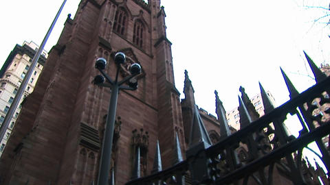 The camera pans up for a worms-eye view of the facade of an old church surrounded by a wrought-iron Footage