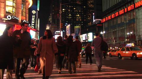 Medium shot of people walking through Times Square at night Stock Video Footage