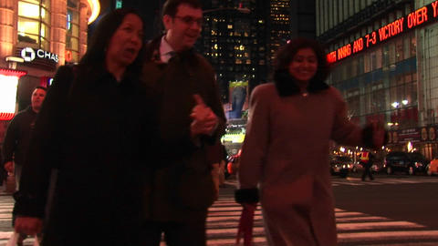 Medium shot of people walking through Times Square at night Stock Video Footage