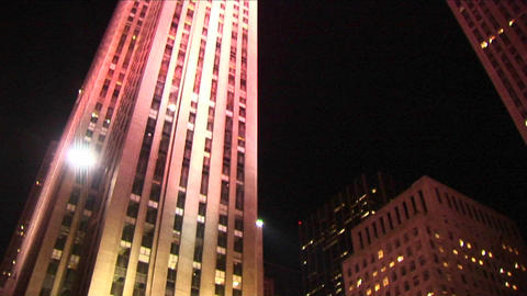 The camera shows skaters at night on the Rockefeller Center ice rink and then pans up the GE Buildin Footage