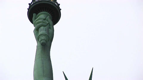 The camera pans from the head and crown of the Statue of Liberty up to the torch Footage