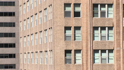 The camera zooms in to a close look at two windows in a large building Footage