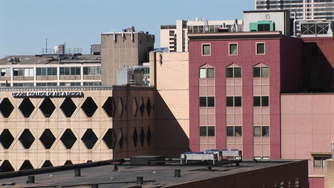 Zoom-in on the windows of a pink multi-story building Footage