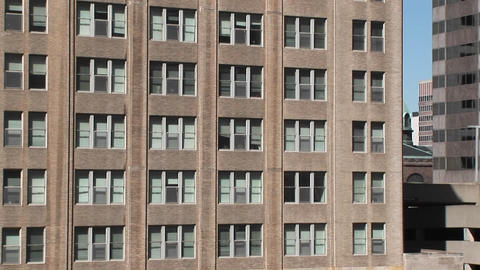 Zoom in to the windows of an older office building to show the blinds askew Footage