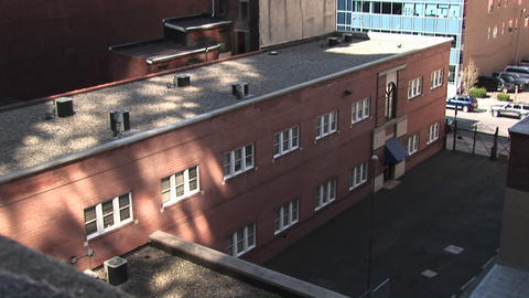 A low, non-descript, brick building is located in the city Stock Video Footage