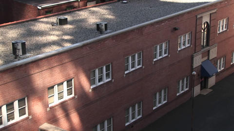 A low, non-descript, brick building is located in the city Footage