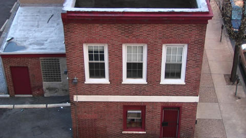The camera looks down on and then zooms in on a small, older two-story building and the windows on t Footage